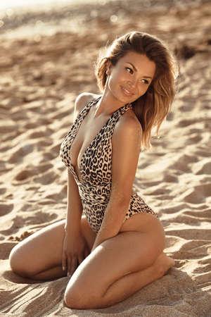 Fashion outdoor photo of sensual bikini model. Carefree Woman Enjoying Beautiful Sunset on the sandy Beach.