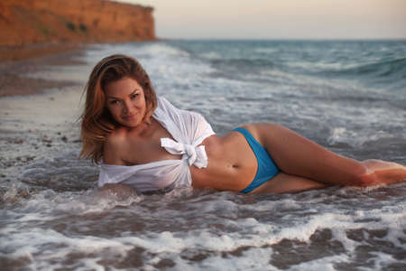 Fashion outdoor photo of sensual wet bikini model in sea waves. Carefree Woman Enjoying Beautiful Sunset on Soft wave of blue ocean. Zdjęcie Seryjne