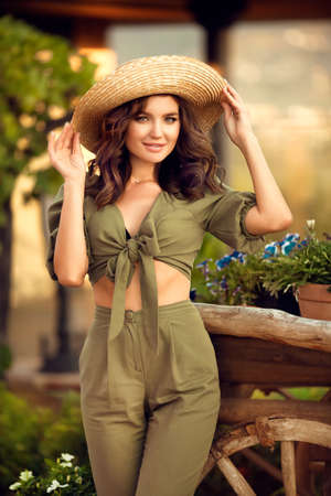 Portrait of beautiful woman smiling with curly hair in hat enjoying at park by wooden cart with green grass and flowers. Sunset photo. Zdjęcie Seryjne
