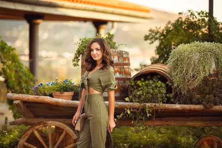 Outdoor Portrait of beautiful woman smiling with curly hair style enjoying at park by wooden cart with green grass and flowers. Sunset photo.