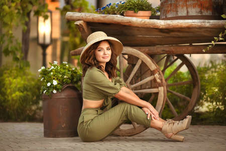Portrait of beautiful woman smiling with hat enjoying at park. Attractive brunette with curly hair sitting by wooden cart with green grass and flowers. Sunset photo.