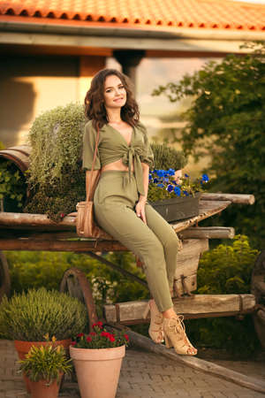 Portrait of beautiful woman smiling with round straw bag enjoying at park by wooden cart with green grass and flowers. Sunset photo.