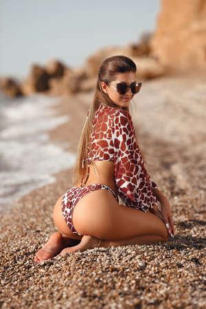 Sexy back of bikini model in fashion swimwear posing on the beach by sea shore. Summer vibes. Outdoor photo.