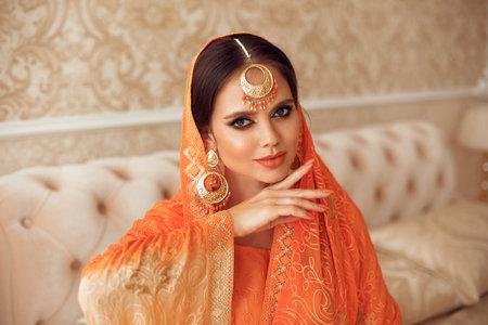 Portrait of beautiful indian girl in traditional saree in luxury interior. Young hindu woman model with kundan golden jewelry set. Indian costume lehenga choli.