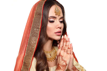 Mehendi. Portrait of beautiful indian girl in traditional saree isolated on white. Young hindu woman model with kundan golden jewelry set. Indian costume lehenga choli. Henna painting hands.