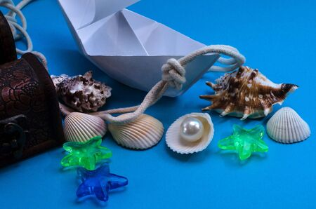 Happy Columbus Day. Paper boat on a blue background with copy space with a sea knot, shells.