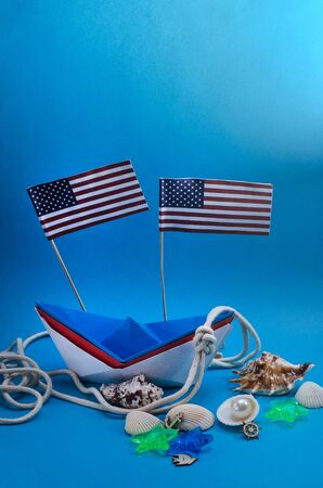 Happy Columbus Day. Paper boat on a blue background with copy space with American flags.