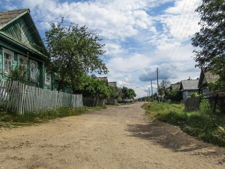 Natural summer landscape. Village street with wooden houses against the sky.against the sky.