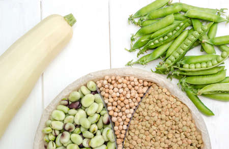 A vegetarian source of protein is lentils, peas, chickpeas, and beans. Top view on a white table. Healthy vegan food.