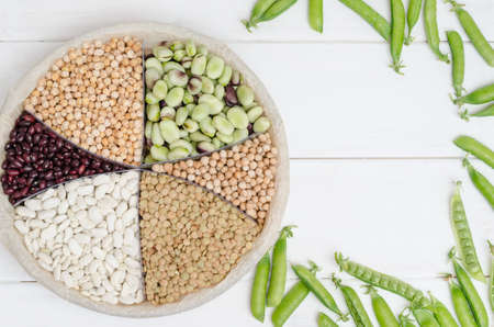 Vegetarian source of protein. Beans, lentils, peas, chickpeas, legumes. Top view on a white table with copy space. Healthy vegan food.