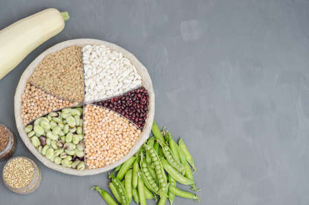 Vegetarian source of protein. Beans, lentils, peas, chickpeas, legumes. Top view on gray background with copy space. Healthy vegan food.