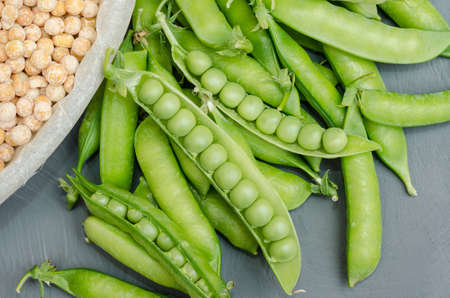 Pods of green peas with yellow dried peas on a gray background close-up. Harvesting in the garden, on the farm 스톡 콘텐츠