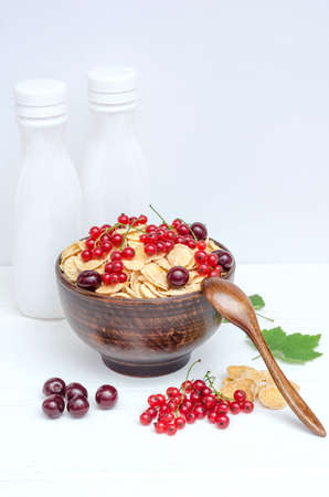 Fresh cornflakes with currants and cherries in a round bowl on a white wooden background.