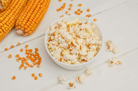Popcorn in a bowl on a white wooden background with ears of corn and grains.