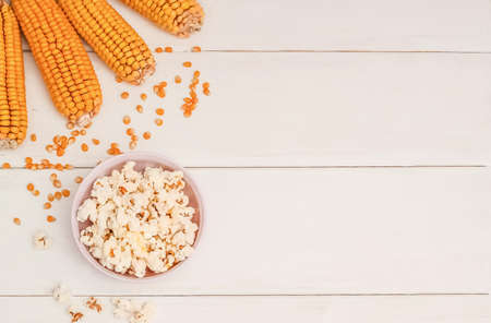 Popcorn in a bowl on a white wooden background with copy space with corncobs and grains.