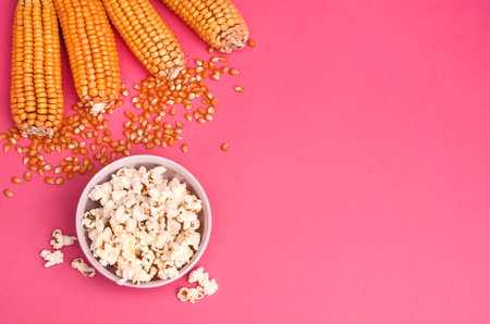 Popcorn in a bowl on a pink background with copy space with corncobs and grains. 스톡 콘텐츠