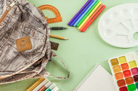 Backpack with school supplies on a green desk background with copy space. Stok Fotoğraf