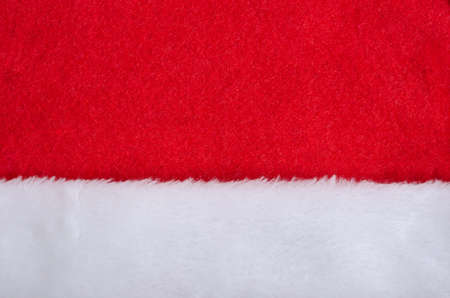 Santa hat red fabric and white fur texture. New Year and Christmas background.