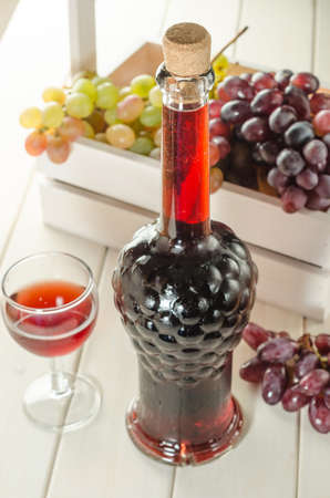 Bottle and glass of red wine with grapes on white wooden background close-up