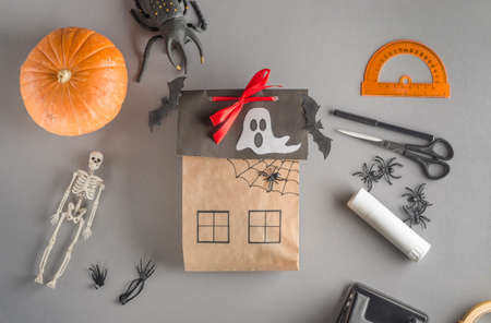Step-by-step wrapping of a gift for Halloween. Step 24 - decorating the Halloween gift house with paper bats