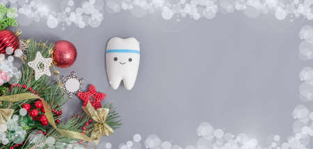 Background banner for dentistry for Christmas and New Year with tooth model on gray background with Christmas decor with copy space.