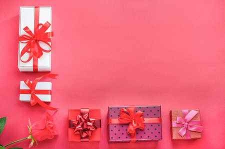 Gifts, backgrounds for Valentine's Day, Mother's Day. Multicolored gift boxes with red ribbons and a rose on a red background with copy space. Holiday sales, congratulations