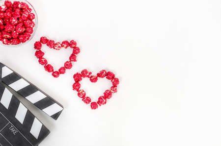 Valentines Day movie concept. Clapperboard with hearts made of red caramel popcorn with copy space 写真素材