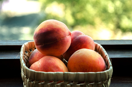 summer peach ripe fruit in a wicker dish with red sides on podkonnike on garden background Stock Photo