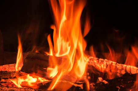 summer night burning wood giving warmth and light on black background Stock Photo