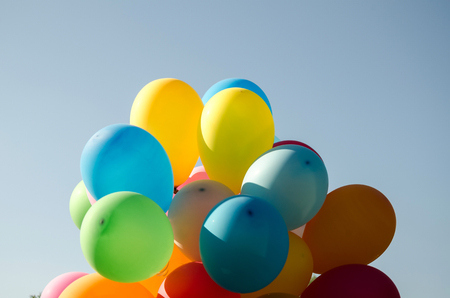 praznichny summer day against a bright blue sky colored armful of colorful inflatable balls Stock Photo