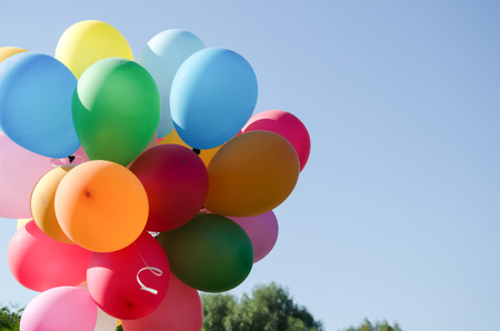 coherent: praznichny summer day against a bright blue sky colored armful of colorful inflatable balls Stock Photo