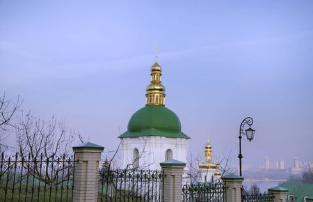A green dome with a golden cross on the territory of the Kiev-Pechersk Lavra, against the backdrop of the city in smog