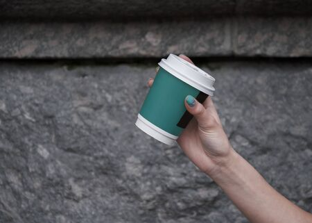 Maiden hand with manicure, against a stone wall background, holding a glass with coffee