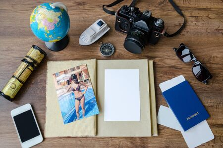 Notepad, credit cards, passport, ticket, luggage, phone and compass on a wooden background, set for travel planning