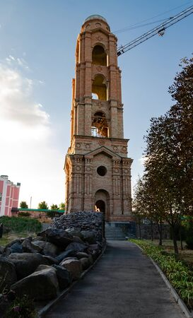 construction of a red brick bell tower on the territory of an Orthodox monastery on a summer day