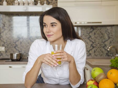 young beautiful girl in a white shirt, in the morning in the kitchen drinking fresh orange juice
