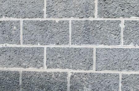 Rectangular gray tile, brick, concrete, fence, close-up for background Stock Photo