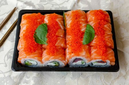 rolls and sushi on a light background, tasty food at home, closeup