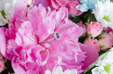 ring with a blue stone in a pink peony, a gift for the holiday, close-up Foto de archivo