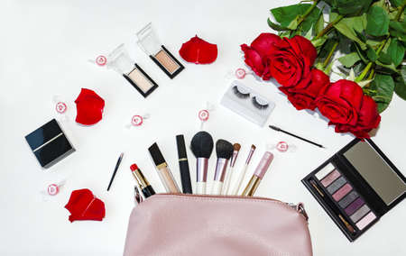 top view of working space with bag and cosmetic brushes, color cosmetics and red roses flowers