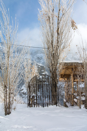 A village house and a metal fence on the road to Geghard Monastery, unique architectural construction and a UNESCO World Heritage in Armenia on cold winter sunny day.