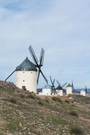 White old windmills on the hill near Consuegra (Castilla La Mancha, Spain), a symbol of region and journeys of Don Quixote (Alonso Quijano) on cloudy day.