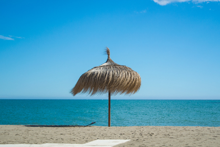 unexplored: A straw umbrella at the beach with perfect sand and blue sea at Torremolinos (Malaga province, Andalusia, Spain).