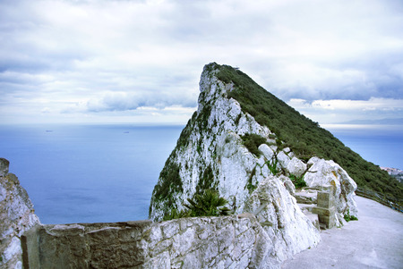 A view of Rock of Gibraltar from an observation desk, Mediterranean sea and a road on cloudy day.