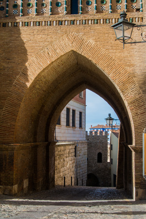 An archway of a mudejar style tower, old buildings and a lantern at the wall at medieval town Teruel at Aragon province, Spain.