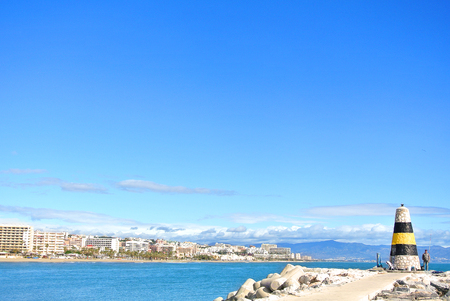 TORREMOLINOS, SPAIN - FEBRUARY 13, 2014: A view to Mediterranean sea, a lighthouse with breakwaters and Torremolinos at the background from a pier at Benalmadena port Puerto Marina, Andalusia, Spain.