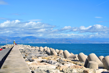 breakwaters: A view to Mediterranean sea, a lighthouse with breakwaters and Torremolinos from a pier at Benalmadena port Puerto Marina, Andalusia, Spain.