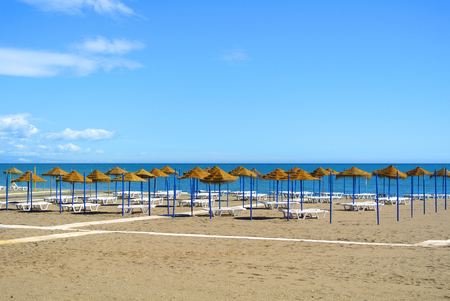 Summer holiday view of a Mediterranean beach prepared for a tourist season, a sandy beach by the blue sea, deckchairs, straw umbrellas and a wooden path at Torremolinos resort on Costa del Sol, Spain. Stock Photo
