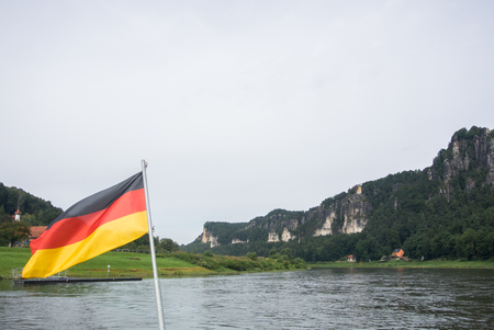 dresden: German flag at ferry through the Elbe at Kurort Rathen village and Bastei rocks at the background, Saxon Switzerland, Germany.