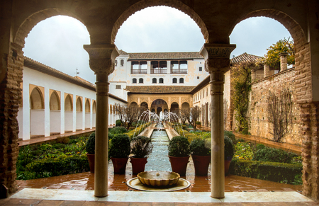 GRANADA, SPAIN - FEBRUARY 10, 2015: An archway to patio with fountains and cutted brushes at Generalife Gardens of Alhambra palace, Granada, Andalusia, Spain.